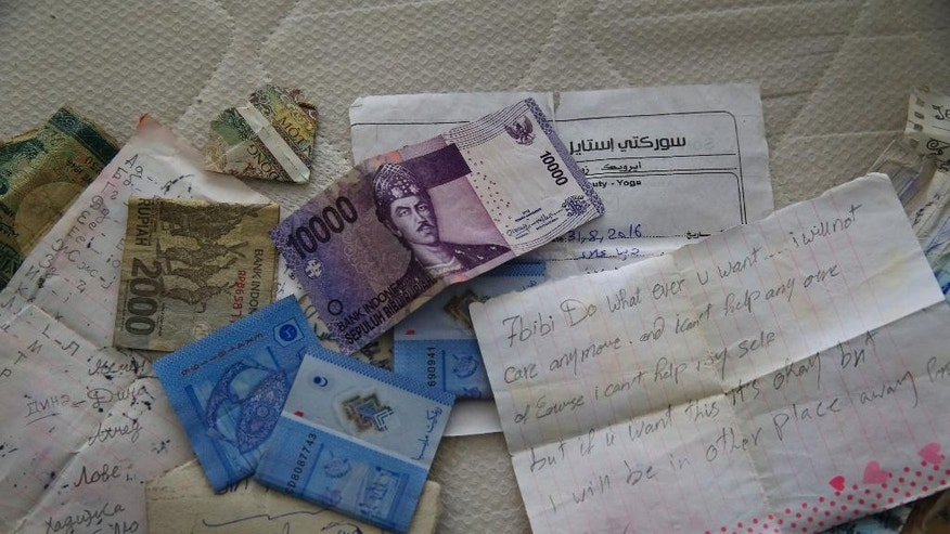 Belongings including banknotes of different currencies are pictured on a bed inside the flat where a suspect of New Year's Day nightclub attack was arrested during an overnight police raid, in Istanbul, Tuesday, Jan. 17, 2017. Turkish police said they captured the gunman who carried out the deadly New Year's nightclub attack in Istanbul, with officials saying Tuesday that he's an Uzbekistan national who trained in Afghanistan and confessed to the massacre.(AP Photo/Lefteris Pitarakis)