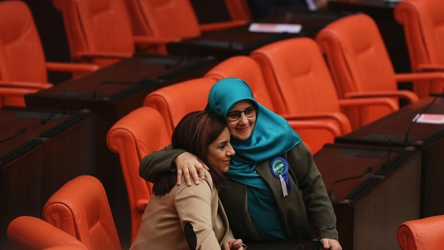 Huda Kaya, right, a legislator with pro-Kurdish Peoples' Democratic Party, (HDP), embraces Selina Dogan, left, of main opposition Republican People's Party (CHP), in the parliament in Ankara, Turkey, prior to deliberations over a controversial package of constitutional amendments that would greatly expand President Recep Tayyip Erdogan's powers, in Ankara, Turkey, Wednesday, Jan. 18, 2017. Legislators on Wednesday resume their deliberations on the proposed amendments which last week resulted in brawls between ruling and opposition party lawmakers. (AP Photo/Burhan Ozbilici)