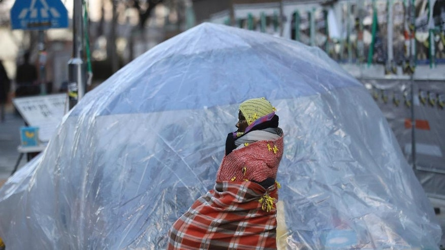 In this Wednesday,  Jan. 11, 2017 photo, a tent made of plastic sheet is set by students to protect a statue of a girl representing thousands of Korean women enslaved for sex by Japan's imperial forces before and during World War II, during a rally in front of the Japanese Embassy in Seoul, South Korea. Some young protesters have been camping for more than a year near the small bronze statue of a girl, determined to protect a symbol that plays an outsized role in the relations between Seoul and Tokyo. (AP Photo/Lee Jin-man)