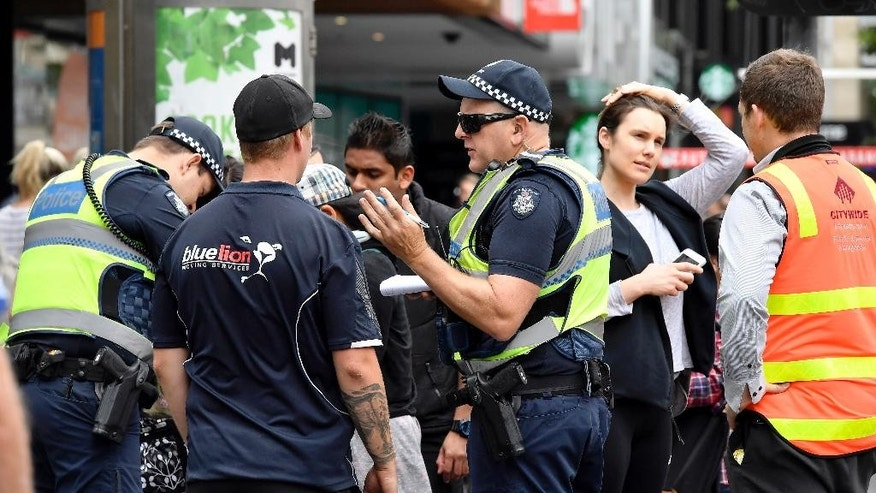 Police listen to witnesses at the scene of an incident in the central business district in Melbourne, Australia, Friday, Jan. 20, 2017. A man deliberately drove into a street crowded with pedestrians on Friday, killing people, police said. Officials said the incident had no links to terrorism. (AP Photo/Andrew Brownbill)
