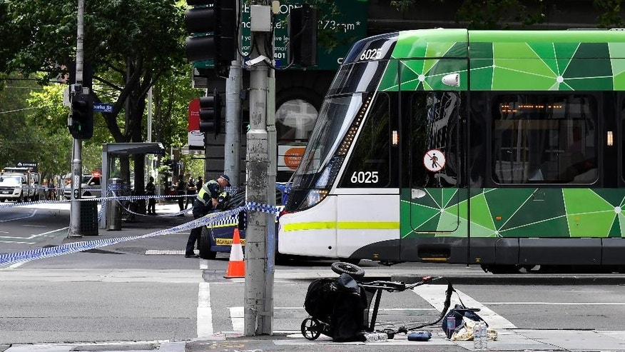 A pram lies upturned on a street in the central business district of Melbourne, Australia, Friday, Jan. 20, 2017. A man deliberately drove into a street crowded with pedestrians on Friday, killing people, police said. Officials said the incident had no links to terrorism. (AP Photo/Andrew Brownbill)