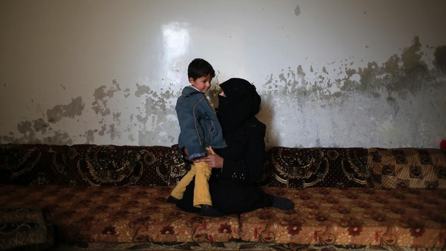 In this Wednesday, Jan. 18, 2017 photo, Elham Saleh, 31, who fled from the village of Deir Hafer, speaks with her son Abdullah, 4, as they sit in a room in the town of Safira, just south of Aleppo, Syria. Saleh, who fled with her son, decided to run away last year after her husband Omar Handoush joined the Islamic State group, a group that the woman says she hated because they badly treat women and are notorious for their public killings. (AP Photo/Hassan Ammar)