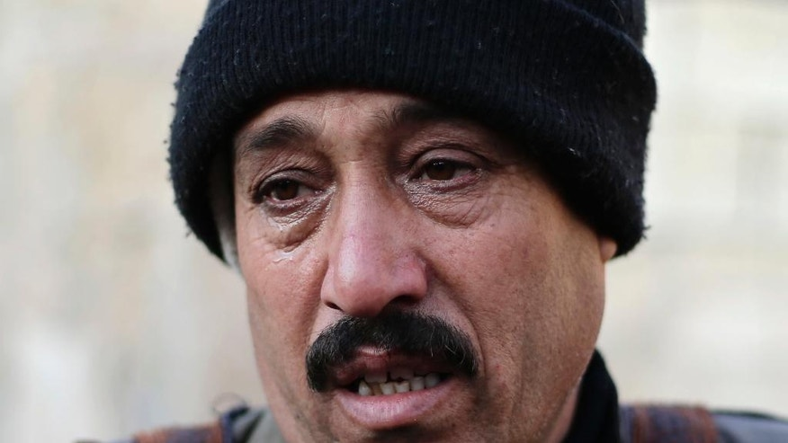 In this Wednesday, Jan. 18, 2017 photo, Nafeh al-Moussa, 49, whose brother, Abdul-Fattah, was beheaded by members of the Islamic State group, cries as he speaks during an interview with the Associated Press in the town of Safira, just south of Aleppo, Syria. Three months after taking him, IS fighters took Abdul-Fattah to the nearby village of Tel Maksour where they read the verdict accusing him of being a spy for the government. Al-Moussa quoted witnesses as saying that her husband's was put head down as a giant man carrying a cleaver chopped of his head, she said holding back her tears. (AP Photo/Hassan Ammar)