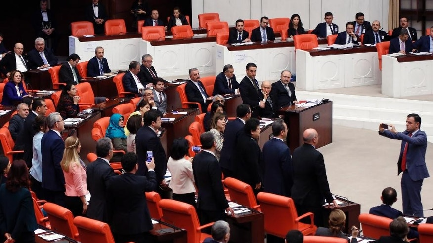 Main opposition Republican People's Party, CHP, lawmaker Baris Yarkadas takes a photo of CHP lawmakers as Turkey's parliament debate proposed amendments to the country's constitution that would hand President Recep Tayyip Erdogan's largely ceremonial presidency sweeping executive powers, in Ankara, Turkey, early Thursday, Jan. 19, 2017. Legislators on Wednesday resume their deliberations on the proposed amendments which last week resulted in brawls between ruling and opposition party lawmakers. (AP Photo)