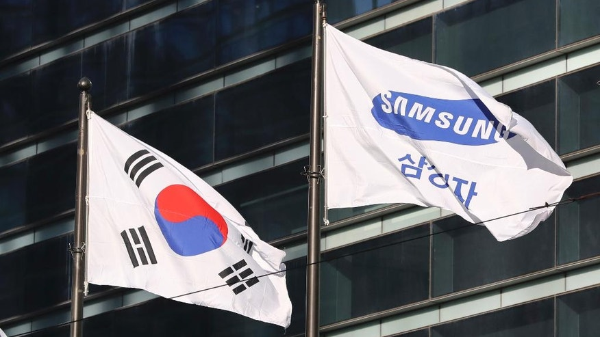 In this Monday, Jan. 16, 2017 photo, the company flag of Samsung Electronics flutters next to the South Korean national flag in Seoul, South Korea. Many South Koreans were shocked at the sight of Samsung Vice Chairman Lee Jae-yong being dragged into custody and then released when a court declined to formally arrest him. Its quite difficult for outsiders to fully grasp how Samsung is inextricably woven into the psychological fabric of this small, proud country. (AP Photo/Lee Jin-man)