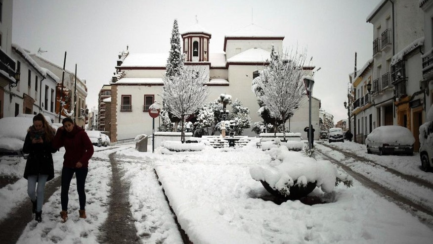 People walk carefully through a street after snowfall in the city of Ronda, southern Spain, Thursday, Jan. 19, 2017. The schools of Ronda, one of the most historical towns of Andalusia, suspended their classes Thursday and traffic has been interrupted on several highways due to the intense snowfall that has fallen during the night. A cold spell has reached Europe with temperatures plummeting far below zero. (AP Photo/Javier Gonzalez)