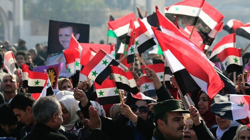 Pro-government supporters hold up the national Syrian flag and pictures of Syrian President Bashar Assad at a gathering at Saadallah al-Jabiri Square in Aleppo, Syria, Thursday, Jan. 19, 2017. Shells slammed into the northern Syrian city of Aleppo Thursday as thousands of government supporters gathered in the main square to celebrate last month's capture of the whole city by the army leading to a disperse by the gathering. (AP Photo/Hassan Ammar)