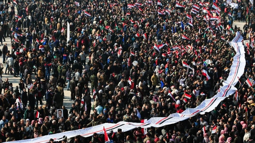 Pro-government supporters hold up a letter directed to Syrian President Bashar Assad at a gathering at Saadallah al-Jabiri Square in Aleppo, Syria, Thursday, Jan. 19, 2017. Shells slammed into the northern Syrian city of Aleppo Thursday as thousands of government supporters gathered in the main square to celebrate last month's capture of the whole city by the army leading to a disperse by the gathering. (AP Photo/Hassan Ammar)
