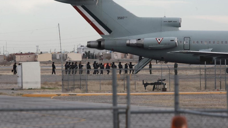 "Police board Mexican Air Force plane after the extradition of drug lord Joaquin ""El Chapo"" Guzman in Ciudad Juarez, Mexico, Thursday, Jan. 19, 2017. Mexico's Foreign Relations Department announced Guzman was handed over to U.S. authorities for transportation to the U.S. on Thursday, the last day of President Barack Obama's administration and a day before Donald Trump is to be inaugurated. (AP Photo/Christian Torres)"