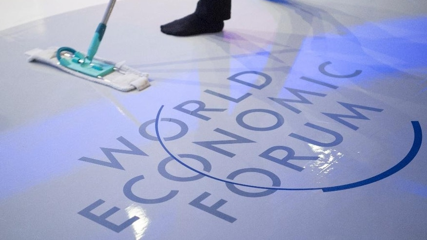 A woman cleans the stage prior to a panel session on the closing day of the 47th annual meeting of the World Economic Forum, WEF, in Davos, Switzerland, Friday, Jan. 20, 2017. (Gian Ehrenzeller/Keystone via AP)