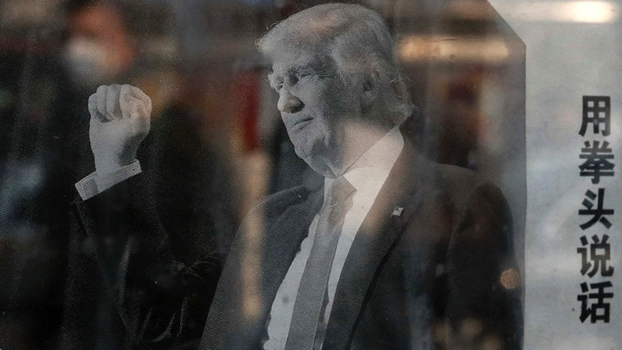 "A man with a mask walking by is reflected on a glass of a public newspaper bulletin board in Beijing posting a photo of U.S. President-elect Donald Trump published on a Chinese newspaper with an article that reads ""Trump uses fist to talk,"""
