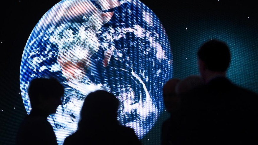 Participants are silhouetted against a picture of the planet Earth on a giant screen during a panel session on the closing day of the 47th annual meeting of the World Economic Forum, WEF, in Davos, Switzerland, Friday, Jan. 20, 2017. (Laurent Gillieron/dpa via AP)
