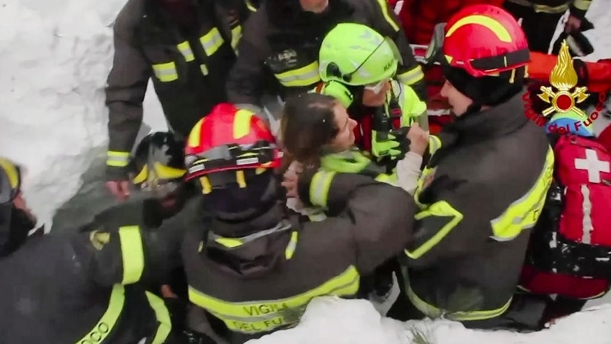 This frame from video shows Italian firefighters pulling out a woman from under the snow and debris.