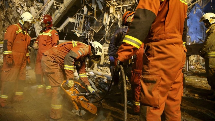 Iranian firefighters start to dig a tunnel to make a corridor under the 17-storey Plasco building which collapsed after being engulfed by a fire, in central Tehran, Iran, Thursday, Jan. 19, 2017. Iran's state-run Press TV says dozens of firefighters have been killed in the collapse of a burning high-rise building. (AP Photo/Ebrahim Noroozi)