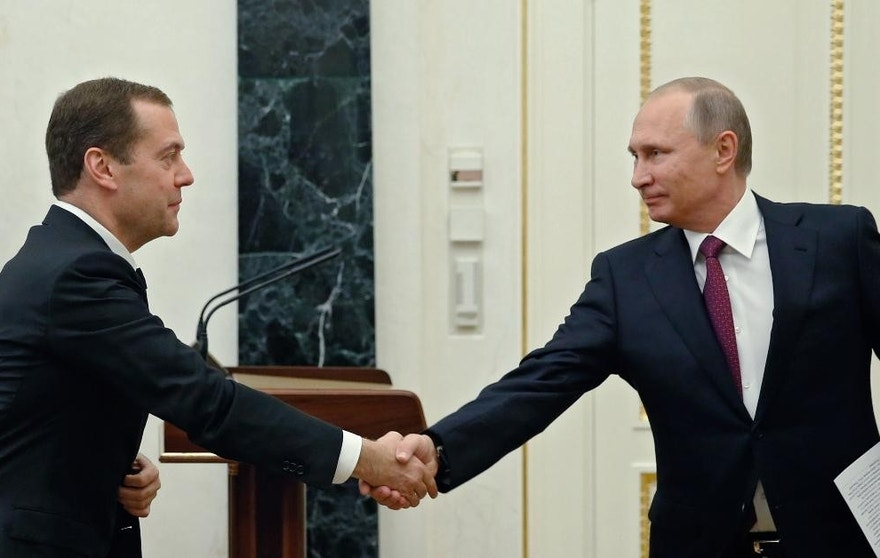 Russian President Vladimir Putin, right, shakes hands with Prime Minister Dmitry Medvedev prior to the Cabinet meeting in Moscow's Kremlin, Russia, on Monday, Sept. 19, 2016. The biggest party supporting President Vladimir Putin scored an overwhelming victory in national parliament elections, winning three-quarters of the seats, the Central Elections Commission reported Monday.(Dmitry Astakhov/ Sputnik, Government Press Service Pool photo via AP )