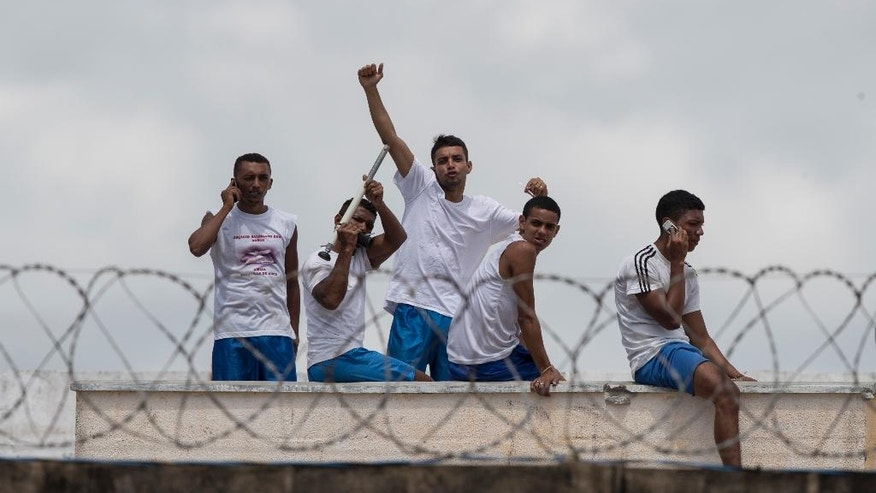 Inmates gesture and talk on cell phones as they stand on the roof of a building amid tension between rival gangs in the Alcacuz prison in Nisia Floresta, near Natal, Brazil, Friday, Jan. 20, 2017. (AP Photo/Felipe Dana)