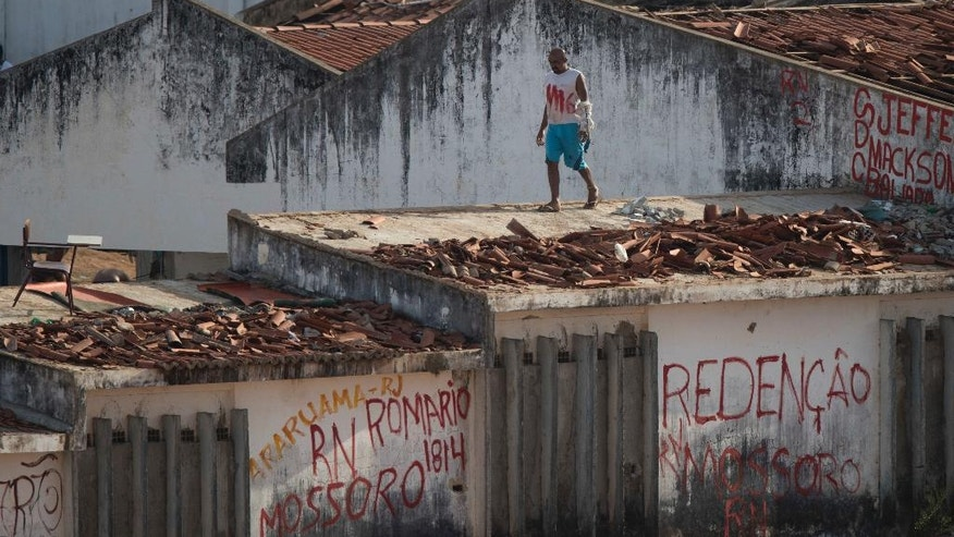 An inmate walks on the roof of a building amid tension as confrontation between rival gangs continue in the Alcacuz prison in Nizea Floresta, near Natal, Brazil, Friday, Jan. 20, 2017. (AP Photo/Felipe Dana)