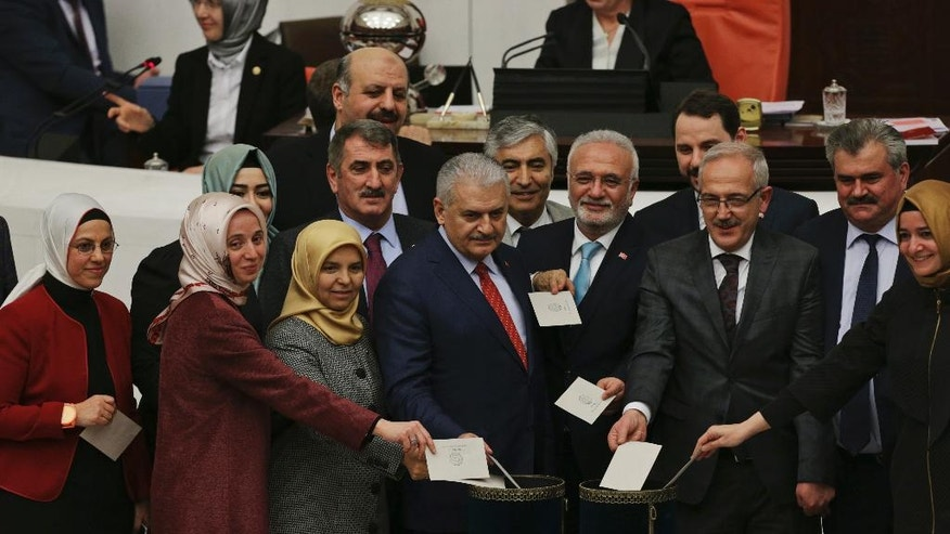 Turkey's Prime Minister, Binali Yildirim, centre, accompanied by some of his lawmakers cast their votes following Turkey's parliament debate proposing amendments to the country's constitution that would hand President Recep Tayyip Erdogan's largely ceremonial presidency sweeping executive powers, in Ankara, Turkey, Friday, Jan. 20, 2017. (AP Photo/Burhan Ozbilici)