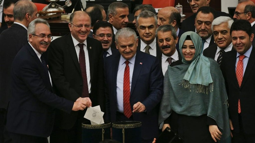Turkey's Prime Minister, Binali Yildirim, centre, accompanied by some of his lawmakers cast their votes during Turkey's parliament debate proposing amendments to the country's constitution that would hand President Recep Tayyip Erdogan's largely ceremonial presidency sweeping executive powers, in Ankara, Turkey, early Saturday, Jan. 21, 2017. (AP Photo/Burhan Ozbilici)