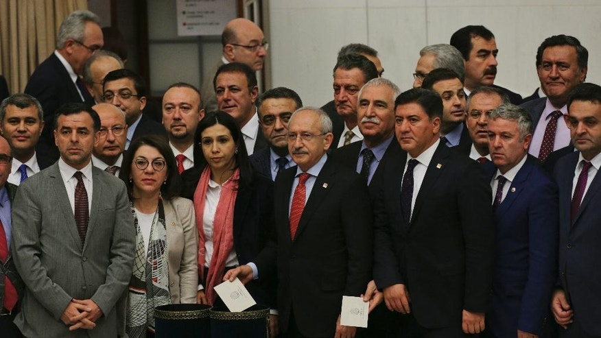 Kemal Kilicdaroglu, centre, leader of Turkey's main opposition Republican People's Party (CHP), accompanied by some of his lawmakers, poses for photographs as they cast their votes during Turkey's parliament debate proposing amendments to the country's constitution that would hand President Recep Tayyip Erdogan's largely ceremonial presidency sweeping executive powers, in Ankara, Turkey, early Saturday, Jan. 21, 2017. (AP Photo/Burhan Ozbilici)
