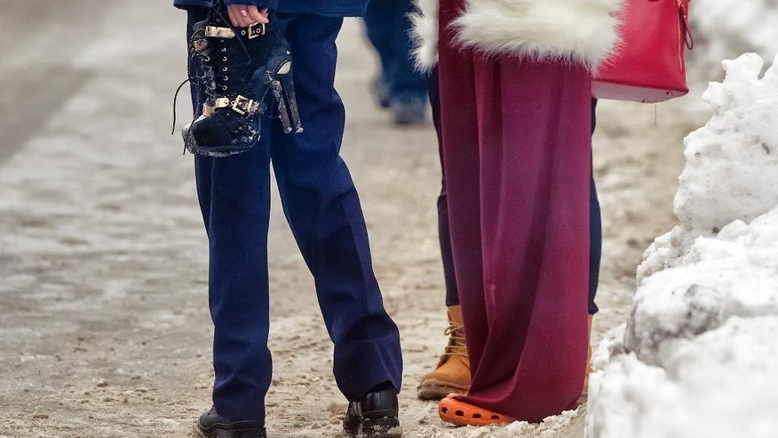 A policewoman holds a pair of high heel boots belonging to a clubber standing next to her who came to retrieve belongings, after firefighters put out a fire that erupted in the early hours at the upmarket Bamboo nightclub, in Bucharest, Romania, Saturday, Jan 21, 2017. Fire engulfed a popular nightclub in the Romanian capital Saturday, sending more than 40 people to hospitals for treatment including one who was seriously injured. No deaths were reported.(AP Photo/Andreea Alexandru)