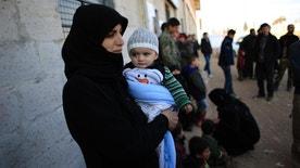 Fatima al-Khalil, 24, and her daughter Qatr al-nada standing outside the Free Legal Support Program office in the shelter in Jibreen, Syria, Saturday, Jan. 21, 2017. Syrian rebels stormed and controlled wide parts of east Aleppo in July 2012 and since then most residents in areas held by insurgents were not able to register themselves because the state had no presence. Those who registered themselves at courthouses run by rebels had documents that are not recognized by the Syrian government does not recognize. (AP Photo/Hassan Ammar)