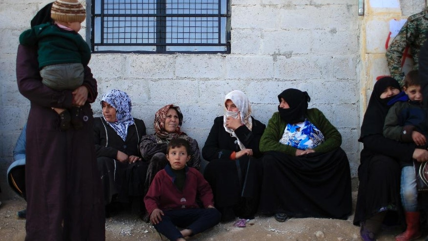 Women standing outside the Free Legal Support Program office in the shelter in Jibreen, Syria, Saturday, Jan. 21, 2017. Syrian rebels stormed and controlled wide parts of east Aleppo in July 2012 and since then most residents in areas held by insurgents were not able to register themselves because the state had no presence. Those who registered themselves at courthouses run by rebels had documents that are not recognized by the Syrian government does not recognize. (AP Photo/Hassan Ammar)