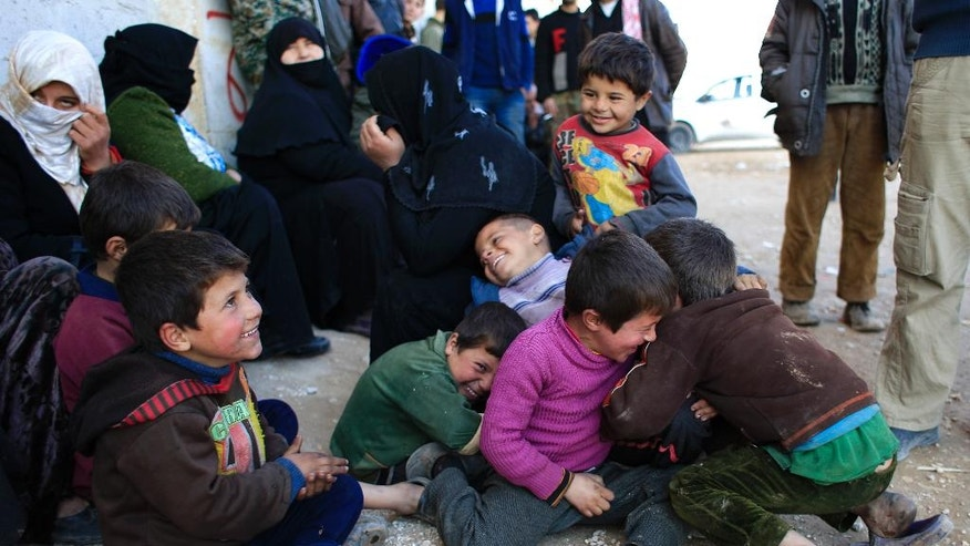 Unregistered children standing with their Family outside the Free Legal Support Program office in the shelter in Jibreen, Syria, Saturday, Jan. 21, 2017. Syrian rebels stormed and controlled wide parts of east Aleppo in July 2012 and since then most residents in areas held by insurgents were not able to register themselves because the state had no presence. Those who registered themselves at courthouses run by rebels had documents that are not recognized by the Syrian government does not recognize. (AP Photo/Hassan Ammar)