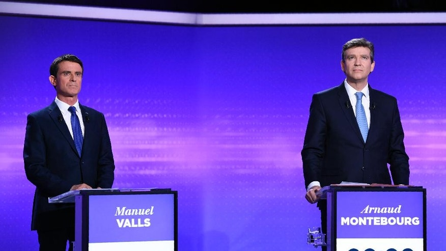 Former Prime minister Manuel Valls, left, and former Economy minister Arnaud Montebourg look on before taking part in a final televised debate of the candidates for the French left's presidential primaries ahead of the 2017 presidential election in Paris in Paris, France, Thursday, Jan. 19, 2017. Seven competitors are bidding to be the Socialist Party's candidate in next spring's French presidential election. (Eric Feferberg/Pool Photo via AP)