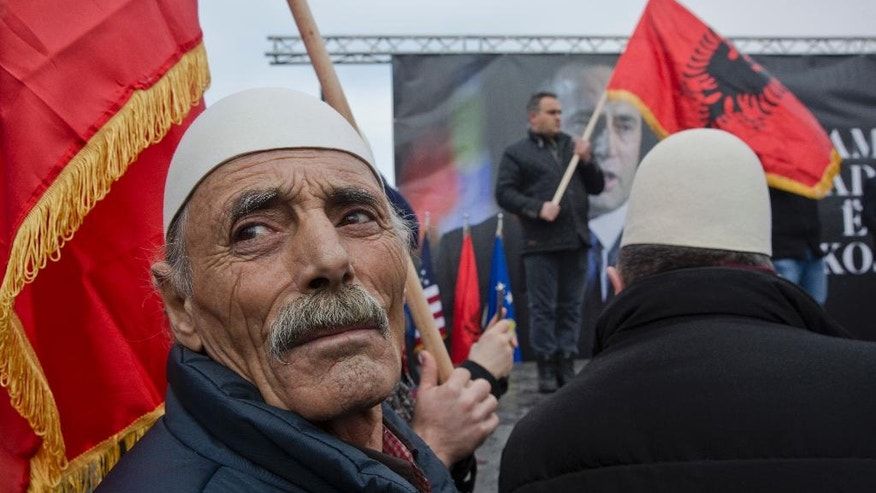 Protesters waving an Albanian flag looks on during a protest demanding immediate release from French judicial supervision of Ramush Haradinaj, Kosovo's former prime minister and a former guerrilla fighter, in Kosovo's capital Pristina on Saturday, Jan 21, 2017. A French court ordered the release of Haradinaj pending a decision on whether to extradite him to Serbia, where he's wanted on war crimes charges. Haradinaj, a former guerrilla fighter in Kosovo's 1998-1999 war for independence from Serbia, was cleared of war crimes charges by a U.N. tribunal. (AP Photo/Visar Kryeziu)