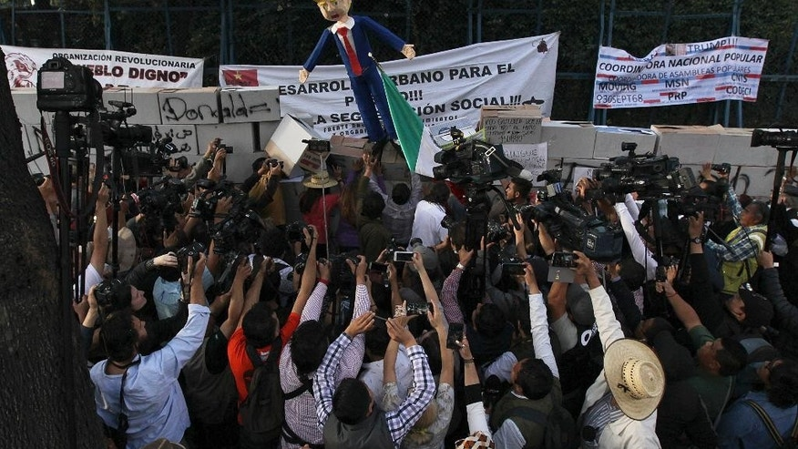 Surrounded by journalists, protesters topple a pinata in the likeness of U.S. President Donald Trump during a protest in Mexico City, Friday, Jan. 20, 2017. Donald Trump became the 45th president of the United States Friday, Jan. 20 2017, amid apprehension in Mexico regarding his previous comments about Mexico and his promise to build a border wall to halt migration. (AP Photo/Marco Ugarte)