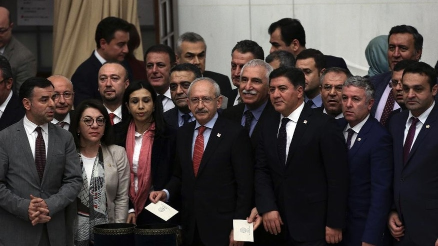 Turkey's main opposition Republican People's Party leader Kemal Kilicdaroglu, center, poses for a photo with his legislators shortly before Turkey's parliament approved a contentious constitutional reform package, paving the way for a referendum on a presidential system that would greatly expand the powers of President Recep Tayyip Erdogan's office, in Ankara, Turkey, early Saturday, Jan. 21, 2017. In an all-night session that ended early Saturday, lawmakers voted in favor of a set of amendments presented by the ruling party, founded by Erdogan.(AP Photo/Burhan Ozbilici)