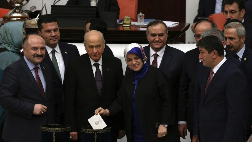 Turkey's opposition Nationalist Movement Party leader Devlet Bahceli, center left, poses for a photo with a ruling party lawmaker, with a scarf, and his legislators,shortly before Turkey's parliament approved a contentious constitutional reform package, paving the way for a referendum on a presidential system that would greatly expand the powers of President Recep Tayyip Erdogan's office, in Ankara, Turkey, early Saturday, Jan. 21, 2017. In an all-night session that ended early Saturday, lawmakers voted in favor of a set of amendments presented by the ruling party, founded by Erdogan.(AP Photo/Burhan Ozbilici)