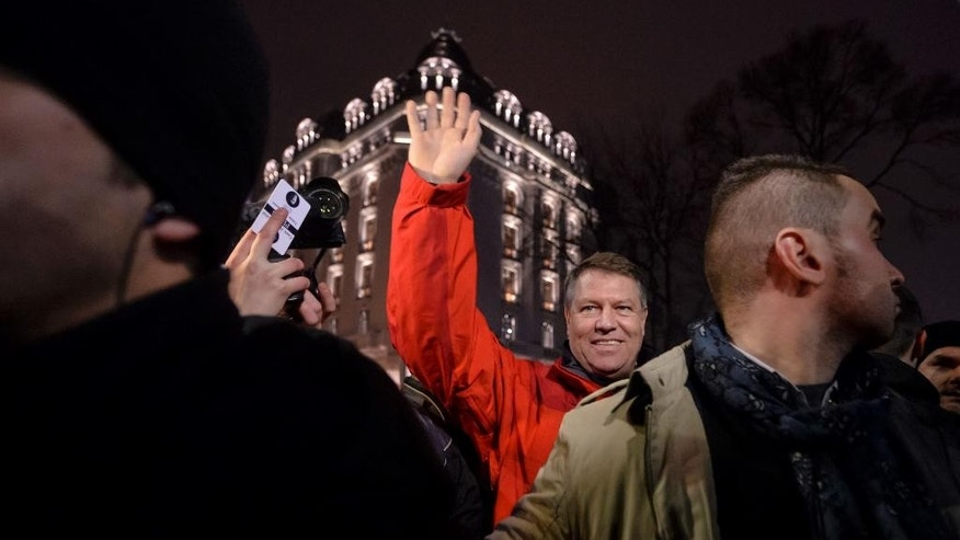 Romanian President Klaus Iohannis waves to the crowd in University Square during a protest against the government's proposal to pardon thousands of prisoners, in Bucharest, Romania, Sunday, Jan. 22, 2017.  Some thousands marched through the streets of the Romanian capital and other cities to protest against the pardon of prisoners which critics say could weaken the anti-corruption fight. (AP Photo/Andreea Alexandru)