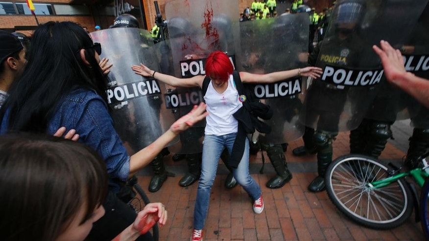 Animal defense activists challenge police ahead of a bullfight, the first such events in four years, outside the Santamaria bullring in Bogota, Colombia, Sunday, Jan. 22, 2017. Bogota's previous mayor banned bullfighting in 2012. But Colombia's constitutional court later overturned the ban, ruling that it was part of Colombia's cultural heritage and couldn't be blocked. (AP Photo/Fernando Vergara)