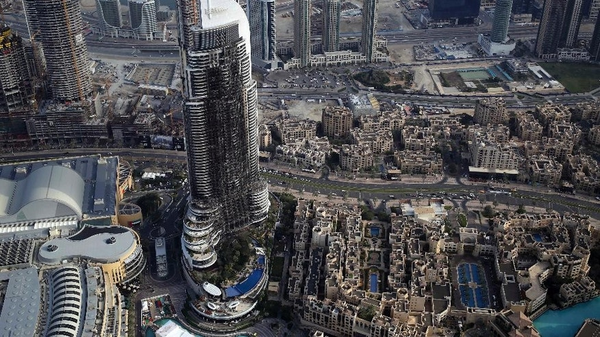 File - In this Sunday, Jan. 10, 2016, photo, the burned hulk of The Address Downtown is seen in Dubai, United Arab Emirates. Dubai authorities announced Sunday, Jan. 22, 2017, that the city-state had new fire safety regulations, but offered few details on how they would be enforced after a series of skyscraper fires. (AP Photo/Jon Gambrell)