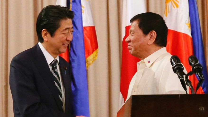 FILE - In this Jan. 12, 2017 file photo, Japanese Prime Minister Shinzo Abe, left, shakes hands with Philippine President Rodrigo Duterte following their joint statement at the Malacanang Palace in Manila during his two-day official visit to the Philippines. China is not happy with Abe's high-profile visits to the Philippines, Australia, Indonesia and Vietnam over concerns that he may be trying to pull the rug under Beijing's efforts to pacify its neighbors in and around the South China Sea. (AP Photo/Bullit Marquez, File)