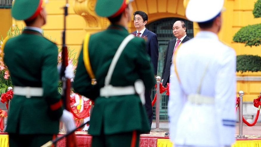 FILE - In this Jan. 17, 2017 file photo, Japanese Prime Minister Shinzo Abe, left in background, and his Vietnamese counterpart Nguyen Xuan Phuc, right in background, review an honor guard at the Presidential Palace in Hanoi during Abe's visit to Vietnam on the last stop of his four-nation tour. China is not happy with Japanese Prime Minister Shinzo Abe's high-profile visits to the Philippines, Australia, Indonesia and Vietnam over concerns that he may be trying to pull the rug under Beijing's efforts to pacify its neighbors in and around the South China Sea. (AP Photo/Minh Hoang, Pool, File)