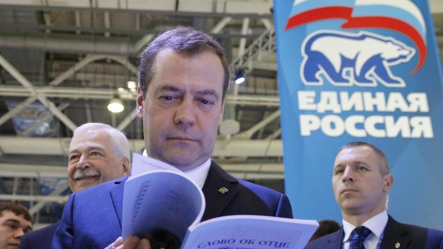 "Russian Prime Minister Dmitry Medvedev, center, reads a book called 'The word of father' as he attends a congress of United Russia Party in Moscow, Russia, Sunday, Jan. 22, 2017. Medvedev says sanctions on Russia are set to remain in place ""for a long time"" despite expectations the election of Donald Trump as U.S. president will lead to a thaw in relations between Washington and Moscow. (Dmitry Astakhov/Sputnik, Government Pool Photo via AP)"
