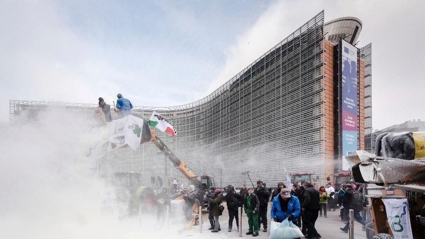 European dairy farmers spray the EU Council building with milk powder to protest the crisis in their sector, in Brussels on Monday, Jan. 23, 2017. The sector has been hit with sagging prices and production costs squeezing profits to the extent that has driven many farmers to the brink of bankruptcy. The EU's executive Commission has approved some support measures over the past year, but the farmers fear that releasing more milk powder on the market would further complicate their plight. (AP Photo/Geert Vanden Wijngaert)