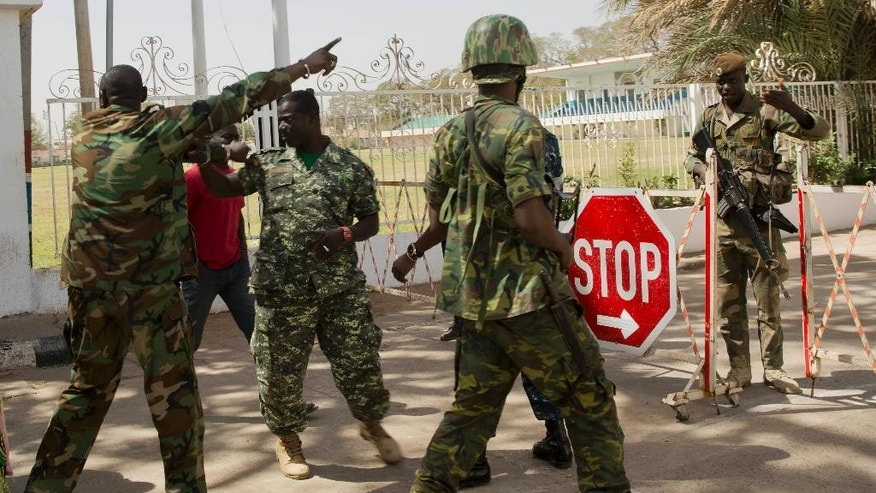 Senegalese troops negotiate with Gambian republican guard, 2nd left, outside the State House in Banjul, Gambia, Monday Jan. 23, 2017, two days after Gambia's defeated leader Yahya Jammeh left the country.  Troops of  Economic Community of West African States  have moved into the State House to prepare for the return of new President Adama Barrow.(AP Photo/Jerome Delay)