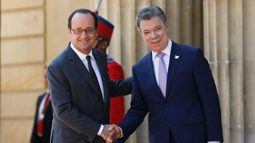 French President Francois Hollande, left, and Colombia's President Juan Manuel Santos, pose for a photo during a welcoming ceremony at the Presidential Palace in Bogota, Colombia, Monday, Jan. 23, 2017. Hollande is on a final Latin America tour before stepping down in a few months after elections to choose his successor. (AP Photo/Fernando Vergara)