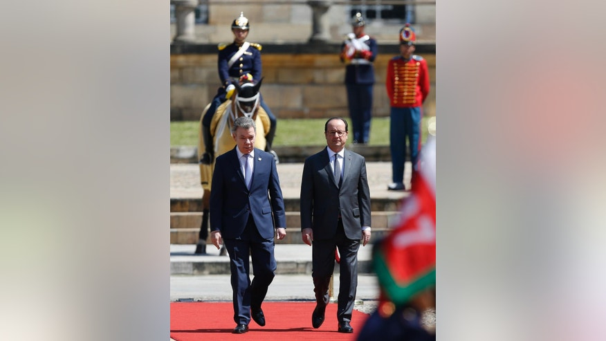 French President Francois Hollande, right, and Colombia's President Juan Manuel Santos, walk on a red carpet as they arrive for a welcoming ceremony at the Presidential Palace in Bogota, Colombia, Monday, Jan. 23, 2017. Hollande is on a final Latin America tour before stepping down in a few months after elections to choose his successor. (AP Photo/Fernando Vergara)
