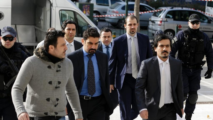 Turkish military officers in suits, center, escorted by Greek police officers, arrive at the Supreme Court in Athens, Monday, Jan. 23, 2017. Greece's highest court will decide later in the day about the extradition of the eight Turkish servicemen, who fled to Greece after a failed July military coup in their country. (AP Photo/Thanassis Stavrakis)