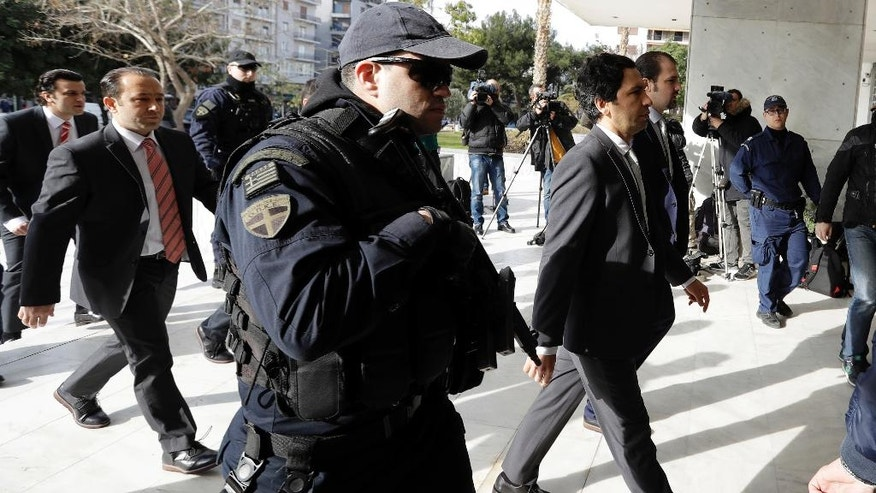 Turkish military officers in suits, left and right, escorted by Greek police, arrive at the Supreme Court in Athens, Monday, Jan. 23, 2017. Greece's highest court will decide later in the day about the extradition of the eight Turkish servicemen, who fled to Greece after a failed July military coup in their country. (AP Photo/Thanassis Stavrakis)