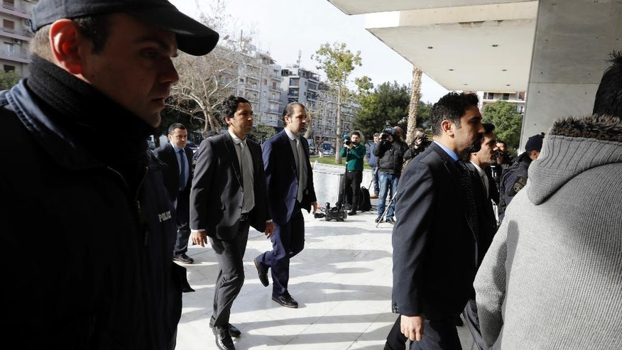 Turkish military officers in suits, center, escorted by Greek police, arrive at the Supreme Court in Athens, Monday, Jan. 23, 2017. Greece's highest court will decide later in the day about the extradition of the eight Turkish servicemen, who fled to Greece after a failed July military coup in their country. (AP Photo/Thanassis Stavrakis)