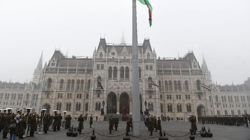 The national flag is hoisted then lowered to half-staff by honour guards during a ceremony to mark the day of mourning observed for victims of the crash of a Hungarian bus in Italy in front of the Parliament building in Budapest, Hungary, Monday, Jan. 23, 2017. A bus carrying Hungarian secondary school students from France back to Hungary crashed on a highway near Verona last Friday night killing 16 and injuring 26 people. (Tamas Kovacs/MTI via AP)