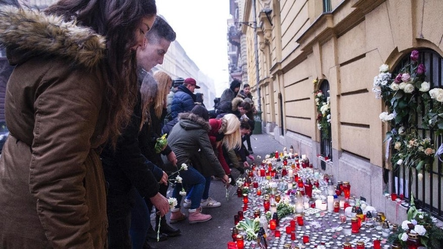 Budapest students light candles and put flowers at a makeshift memorial outside Szinyei Merse Pal Secondary School to pay tribute to victims of the crash of a Hungarian bus in Italy in Budapest, Hungary, Monday, Jan. 23, 2017. Hungary observes a day of national mourning after a bus carrying students of this secondary school from France back to Hungary crashed on a highway near Verona last Friday night killing more than a dozen people. (Bea Kallos/MTI via AP)