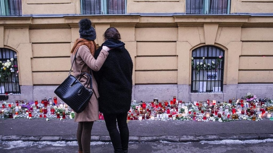 A survivor, right, is embraced by another girl as they stand at a makeshift memorial outside Szinyei Merse Pal Secondary School to pay tribute to victims of the crash of a Hungarian bus in Italy in Budapest, Hungary, Monday, Jan. 23, 2017. Hungary observes a day of national mourning after a bus carrying students of this secondary school from France back to Hungary crashed on a highway near Verona last Friday night killing  more than a dozen people.  (Bea Kallos/MTI via AP)