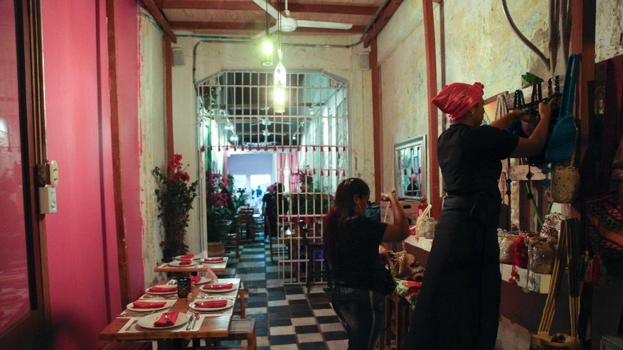 In this Jan. 13, 2017 photo, inmates work in the dining room of the Interno restaurant at the San Diego prison, in Cartagena, Colombia. Convicts have been serving up gourmet meals at the Interno in the all-women prison since December, in a novel experiment intended to promote the inmates' rehabilitation and confront the Colombian public's neglect of the country's exploding prison population. (AP Photo/Alba Tobella)